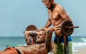 picture of weight-lifting  - Two men doing weight lifting on sea beach - JPG