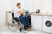 pic of handicap  - Young Handicapped Man On Wheelchair Cleaning Induction Stove - JPG