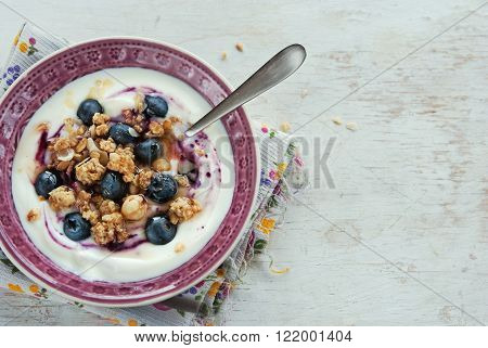A bowl of yogurt with blueberries cereals granola topped with honey on a wooden white table healthy breakfast
