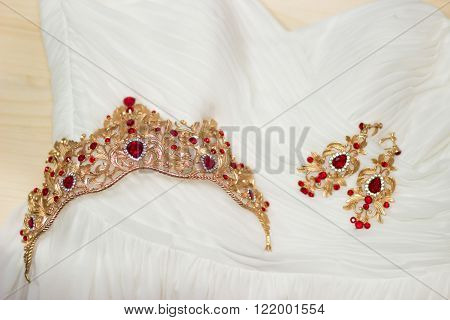 Bride golden crown with shining brilliants on wedding dress
