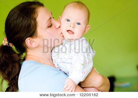 mother kiss her baby on green background