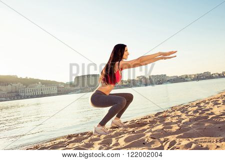 Healthy Cheerful Woman Squating On The Open Air, Side View Photo