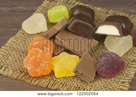 Jelly candy and chocolate on the tablecloth. Sweets for children.