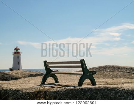 Bench with lighthouse at Peggy´s Cove, Nova Scotia with view onto the sea.