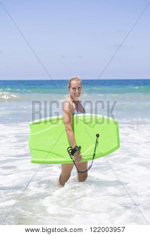 Attractive woman boogie boarding in the ocean waves