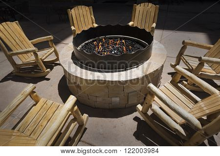 Large outdoor fire pit surrounded by wooden rocking chairs