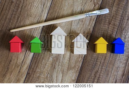 concept of painting works. wooden houses of the toy bricks and brush symbolizes the work of a painter