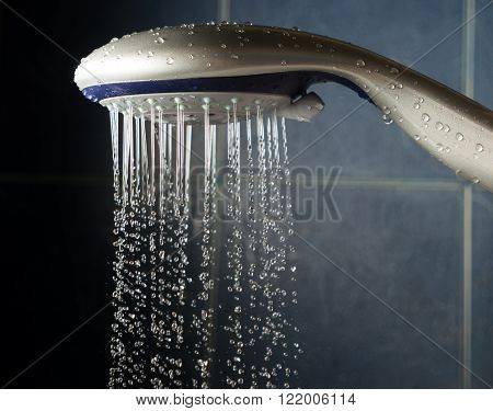 Shower head with stream of small water drops on dark blue background