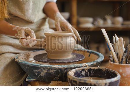 Hands of a potter makes a pot