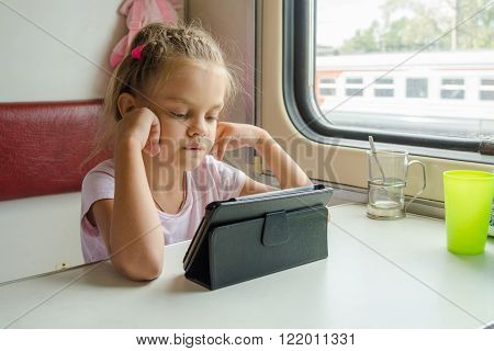 Girl Looking At The Tablet In The Train