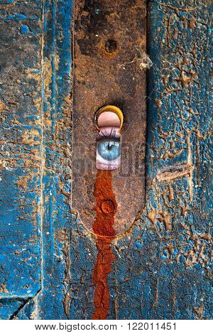 Women eye staring through the old keyhole