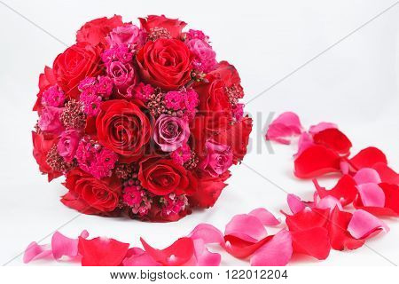 Red and hot pink wedding bouquet of roses on white background