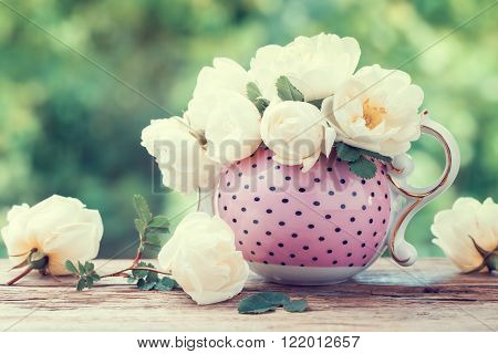 Bouquet of roses in tea kettle. Wedding or birthday still life. Retro styled.