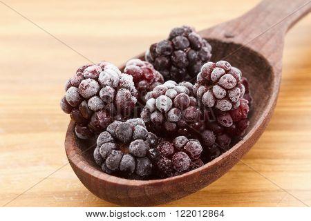 Macro view on frozen Blackberry fruits in spoon wooden background