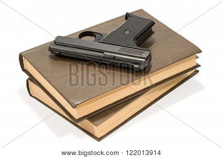 Black small gun lying on a stack of two brown books isolated on white background