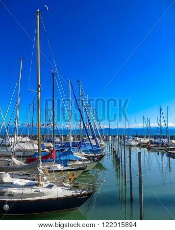 Lake Constance, Germany - August 7, 2015: Tall sail boats docked in a harbour on water at Lake Constance (Bodensee) on a sunny day