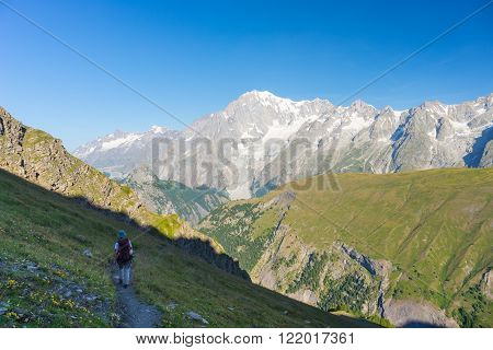 Hiker walking uphill on footpath with great panoramic view over the Mont Blanc massif and mountain peak (4810 m). Backpacker's summer adventures and wanderlust in Valle d'Aosta Italian French Alps.