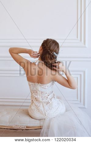 Sensitive young bride with long brown hair and green eyes wearing an engagement ring