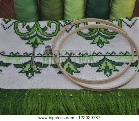 cross-stitch embroidery frame wooden towel in bright green thread on a background of a wooden table