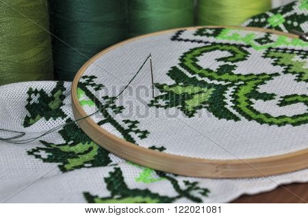 Embroidered towel traditional wooden hoop on the background of a wooden table