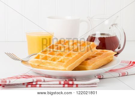 Fresh made waffles with maple syrup coffee and juice.