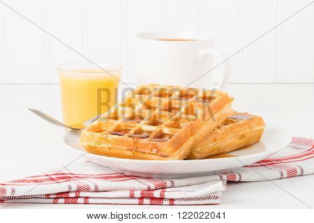 Fresh made waffles and maple syrup served with juice and coffee.