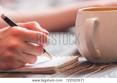 Girl writing with pen in diary on brown wooden table