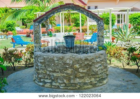 Cayo Coco island, Cuba, Sep 2, 2015, view of old natural vintage stone will with pail standing in foreground of outdoor spa tropical garden