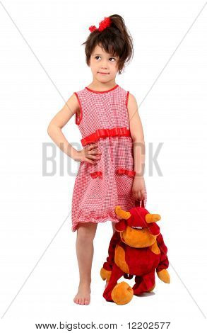 Crafty smiling little girl standing with cow toy in hand