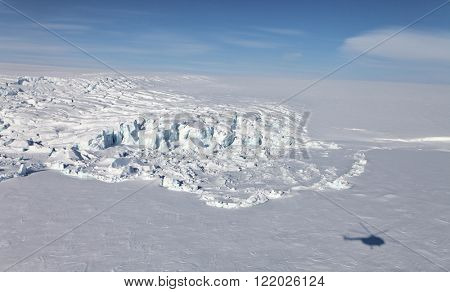 Flowing glacier and helicopter shadow . Aerial view. Arctic region