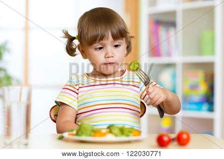 Little girl examines Brussels sprouts. Child with healthy food sitting at table in nursery