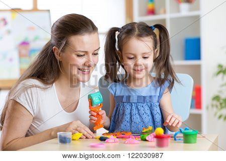 Mother and kid daughter at home molded from clay and play together. Concept of preschool or home edu