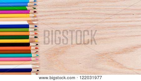 Colorful pencils left side of frame on oak wood desktop. Plenty of copy space.