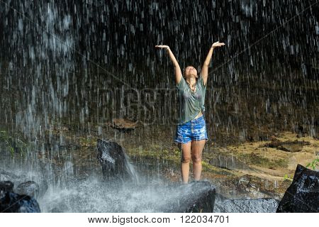 Ecstatic dressed woman under tropical waterfall, Thailand