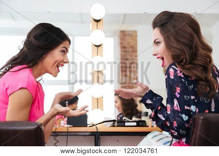 Two surprised young women sitting and talking in beauty salon