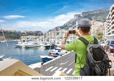 Tourist in Monaco taking photo of yachts in the Port Hercules area