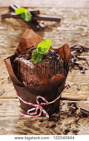 chocolate muffin with mint leaves on a wooden table