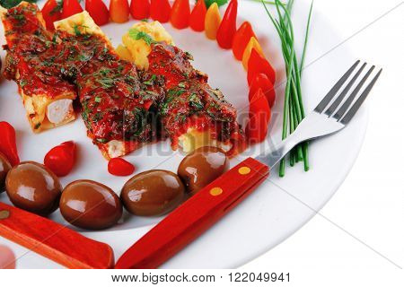 cheese cannelloni served with pepper and tomato on white plate