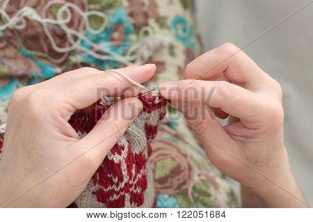 Sitting woman hands  needle knitting snowflake pattern
