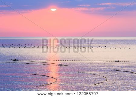 Sunrise And Fishing Nets On Sea Surface.