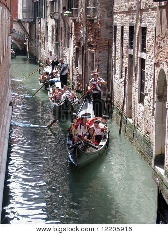 Three gondolas taking tourists through canals of Venice. Summer 2004. Editorial use only.