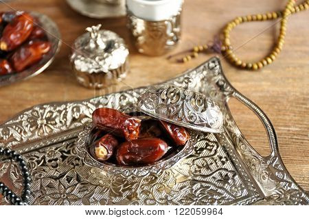 Composition of dried dates in holiday dish and rosary on wooden background closeup