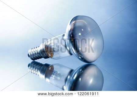 Blackout concept. One electric bulb with reflection on gray background