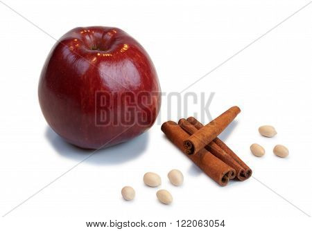 Red apple, cinnamon and peanuts on a white background