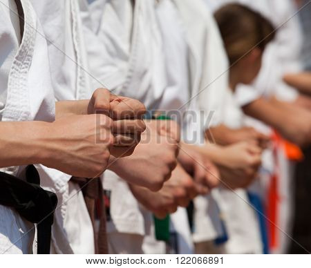 Karate practitioners fist in focus against other blurred karate practitioners during training