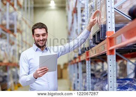 wholesale, logistic, business, export and people concept - happy man or manager with tablet pc computer checking goods at warehouse