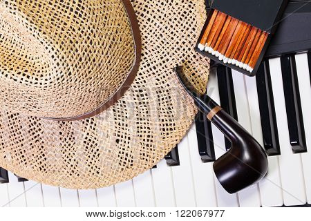 Detail of piano keyboardstraw hat and luxury pipe