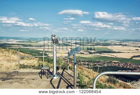 Sightseeing binoculars and slovak landscape with fields and clouds. Nitra Slovakia. Tourism theme.