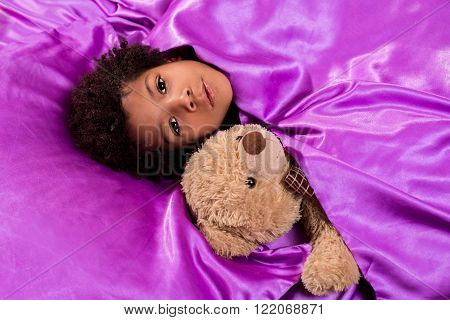 Black kid with teddybear. Child in bed with teddybear.