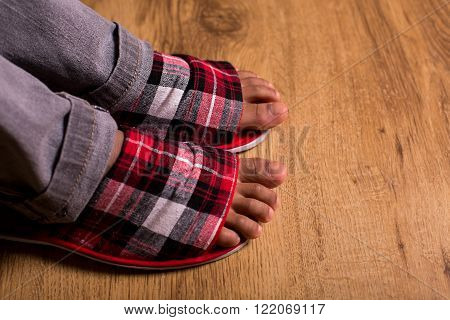 Feet in slippers and pants. Gray pants with checkered slippers.